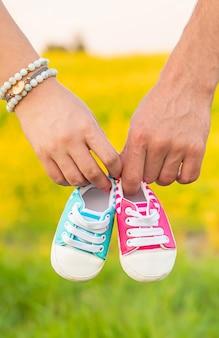 Femme enceinte et homme tiennent des chaussures de bébé