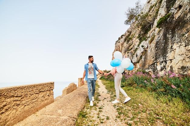 Femme enceinte jeune beauté saine avec son mari et ballons en plein air