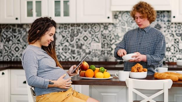 Une femme enceinte joyeuse avec des dreadlocks boit du thé et regarde son mari frisé préparer le petit-déjeuner