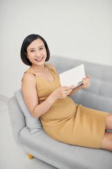 Femme enceinte, lecture livre, dans, salle de séjour