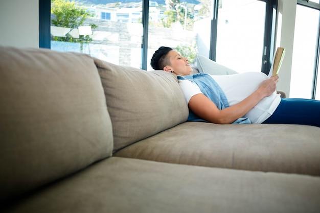 Femme enceinte, lisant un livre, allongée sur un canapé dans le salon