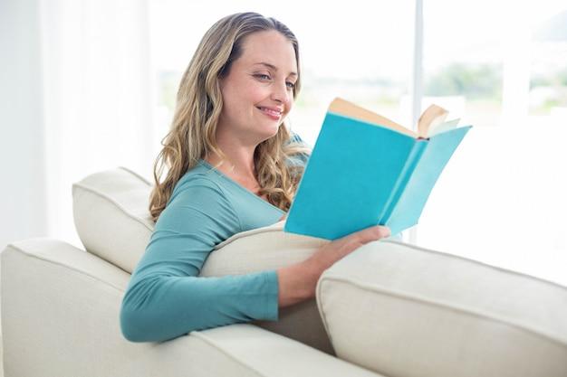 Femme enceinte en lisant un livre sur le canapé