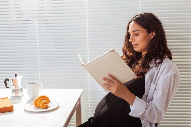 Une femme enceinte lit un livre pendant le petit-déjeuner. concept de grossesse et d'éducation