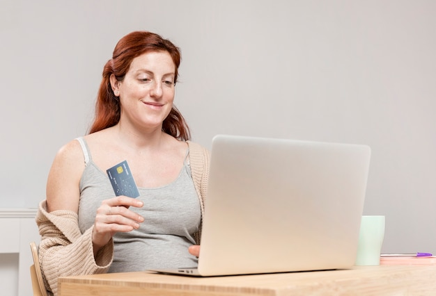 Femme enceinte à la maison faisant des achats en ligne