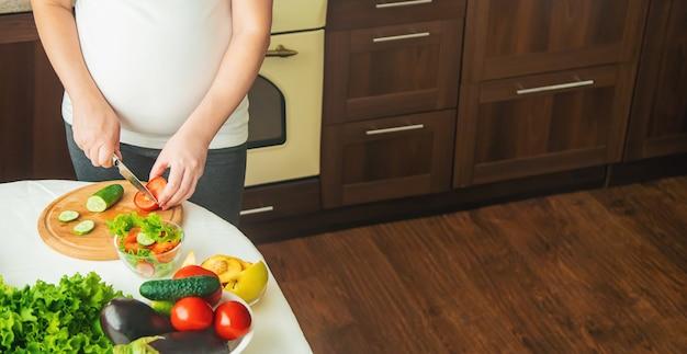 Une femme enceinte mange des légumes et des fruits