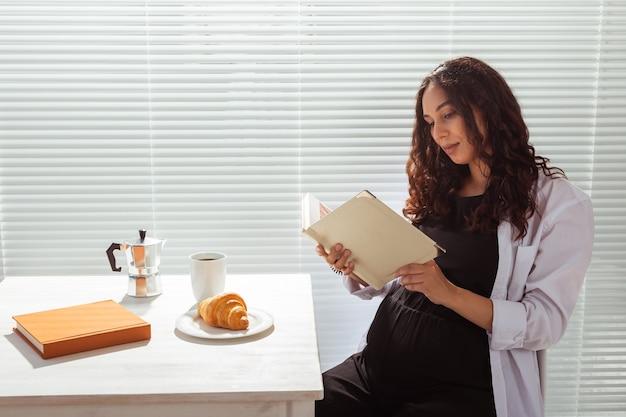 Femme enceinte mangeant et lisant un livre à la maison. concept du matin, du petit-déjeuner et de la grossesse.
