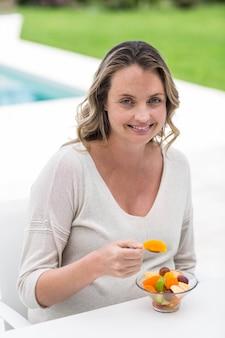 Femme enceinte mangeant une salade de fruits au bord de sa piscine