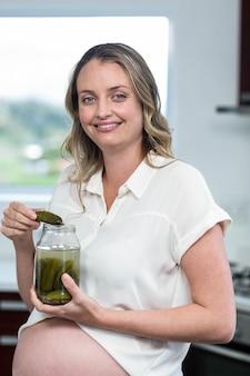 Femme enceinte manger des cornichons dans la cuisine