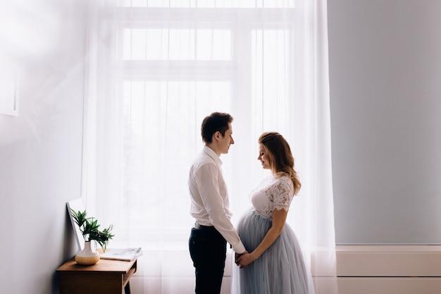 Femme enceinte, à, mari, devant, fenêtre