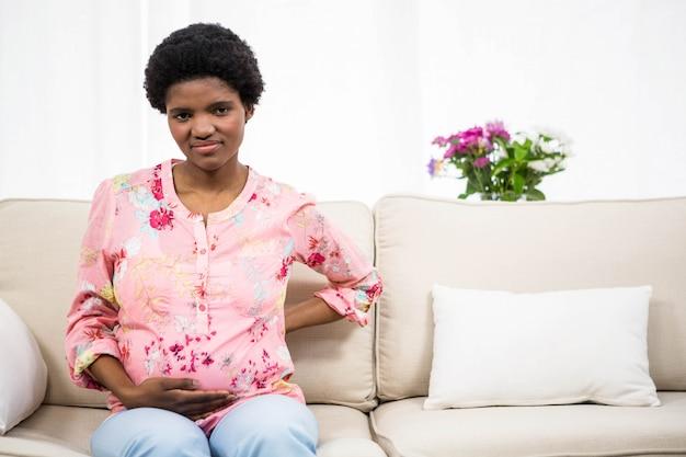 Femme enceinte avec maux de dos sur canapé