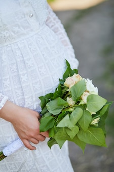 Femme enceinte méconnaissable touchant le ventre, tenant le bouquet