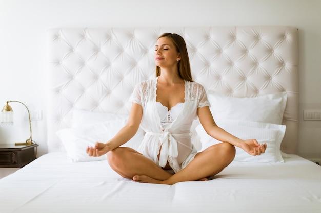 Femme enceinte méditant et pratiquant le yoga dans sa chambre