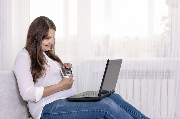 Une femme enceinte montre une image échographique d'un enfant à naître via un lien vidéo