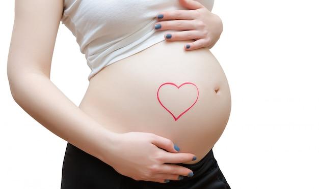 La femme enceinte sur mur blanc coeur peint sur le ventre.