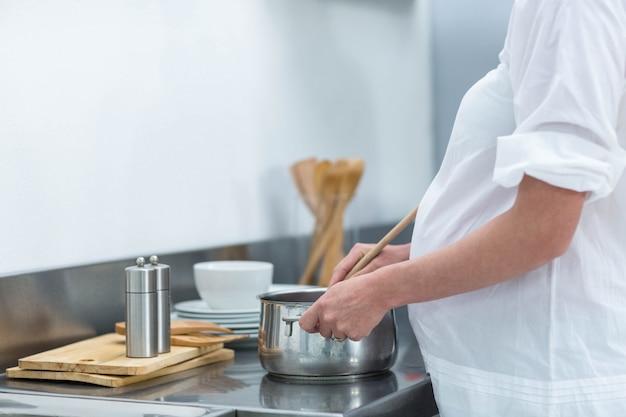 Femme enceinte occupée dans la cuisine à préparer des aliments