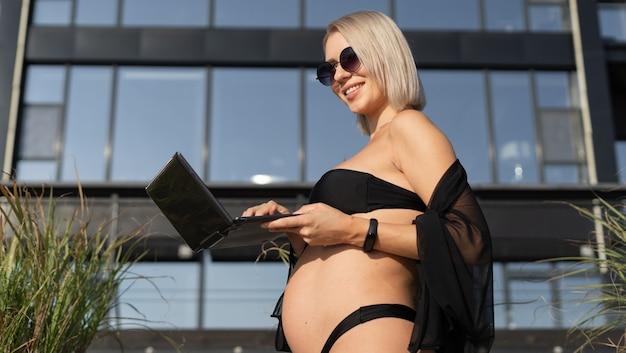 Une femme enceinte avec un ordinateur portable dans les mains tape du texte. des lunettes de soleil. espace de copie