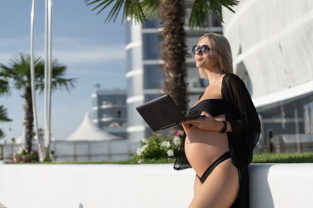Femme enceinte avec un ordinateur portable dans ses mains. espace de copie