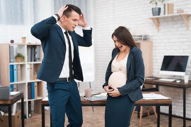 Femme enceinte à partir de la naissance au bureau de travail