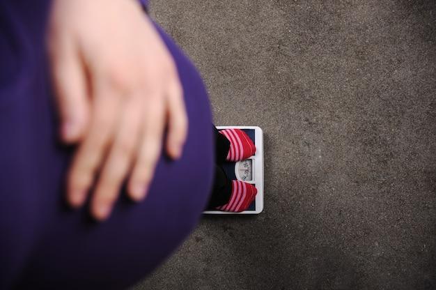 Femme enceinte pesant à l'échelle