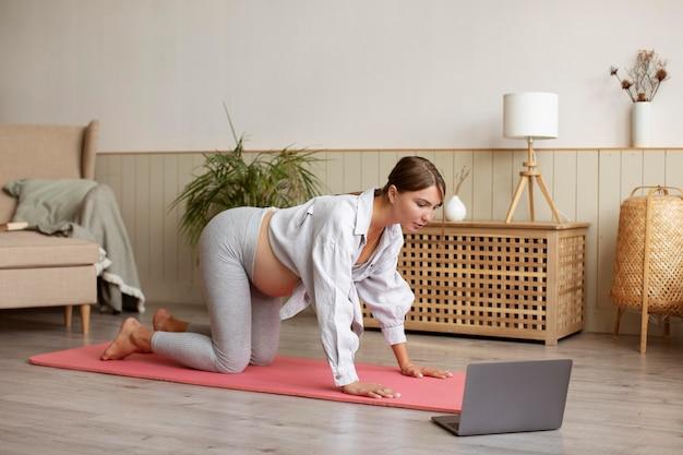 Femme enceinte pratiquant le yoga à la maison