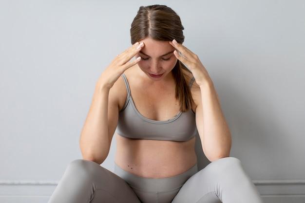 Femme enceinte prenant une pause de l'exercice à la maison