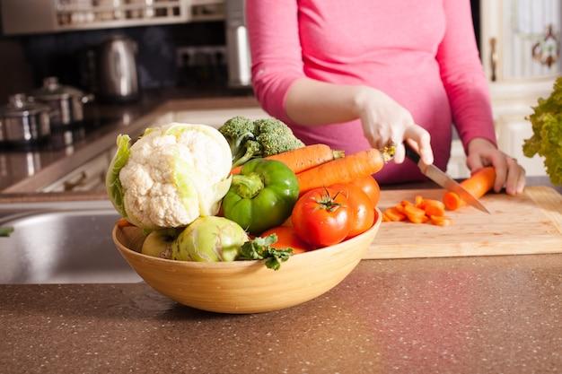 La femme enceinte prépare des plats dans la cuisine