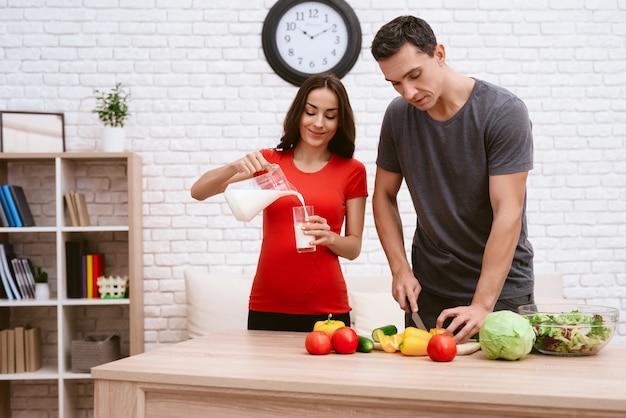 Une femme enceinte prépare des plats avec son mari.