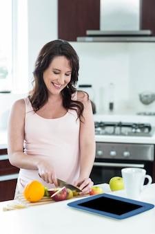 Femme enceinte prépare son petit déjeuner dans sa cuisine