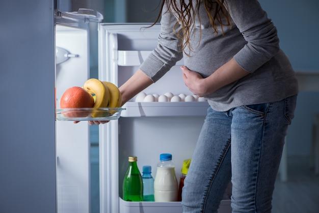 Femme enceinte près du réfrigérateur à la recherche de nourriture et de collations dans la nuit