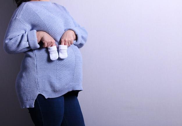 Femme enceinte en pull bleu tenant des chaussettes de bébé blanc à la main. image de la grossesse et de la maternité.