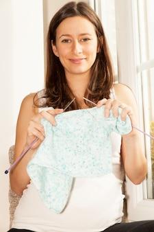 Femme enceinte qui a tricoté des vêtements de bébé