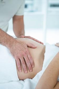 Femme enceinte recevant un massage de l'estomac par un masseur au centre de bien-être