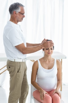 Femme enceinte recevant un massage de la tête d'un masseur à la maison
