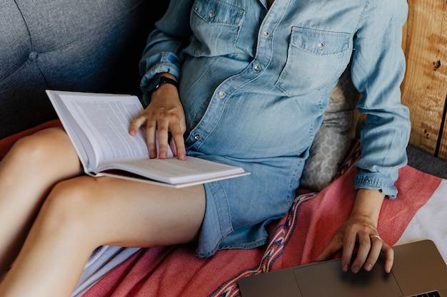 Femme enceinte recherchant sur un site web à partir de son ordinateur portable tout en lisant un livre sur un canapé