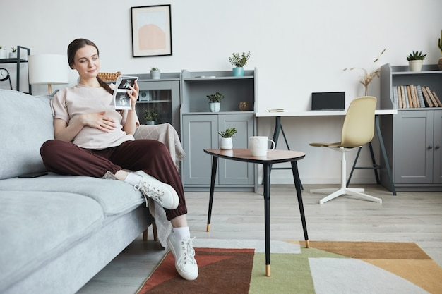 Femme enceinte reposant sur un canapé avec une image radiographique de son bébé dans le salon