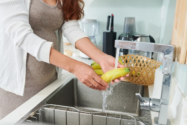 Femme enceinte, rinçage des bananes