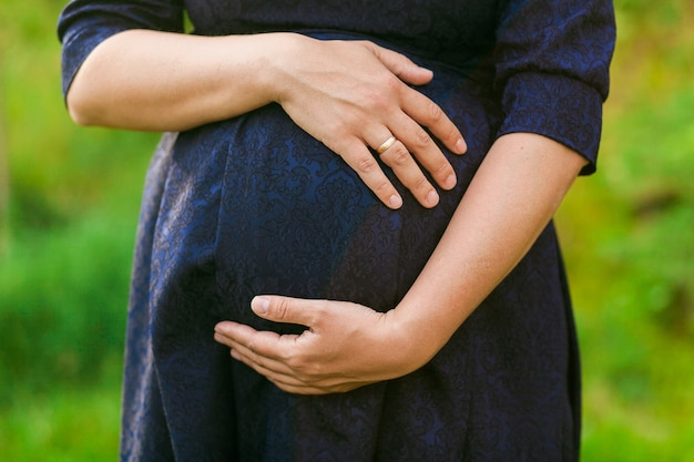 Femme enceinte en robe noire sur fond d'herbe verte