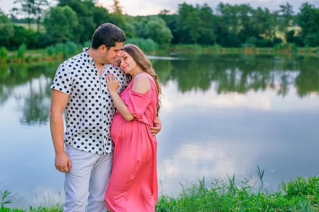 Femme enceinte en robe rose et son mari embrassant près du lac.