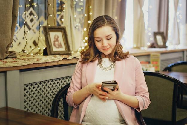 Une femme enceinte se caresse l'estomac.