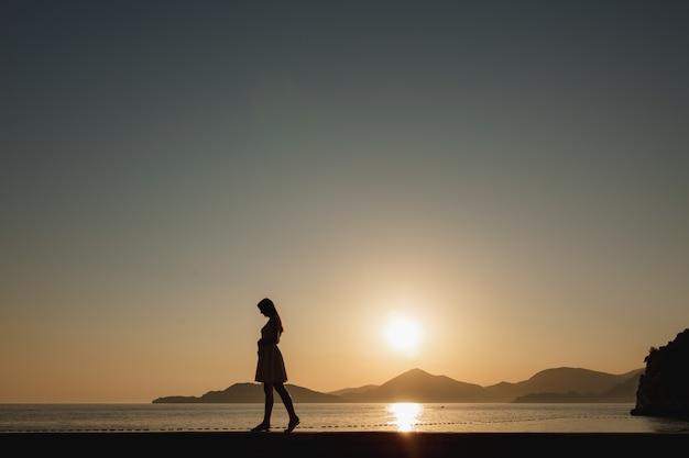Une femme enceinte se promène au bord de la mer au coucher du soleil et lui caresse doucement le ventre, derrière elle se trouvent les montagnes et le soleil couchant.