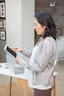 Femme enceinte sérieuse avec tablette dans le salon