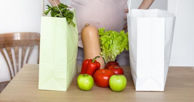 Femme enceinte sortir des légumes du panier