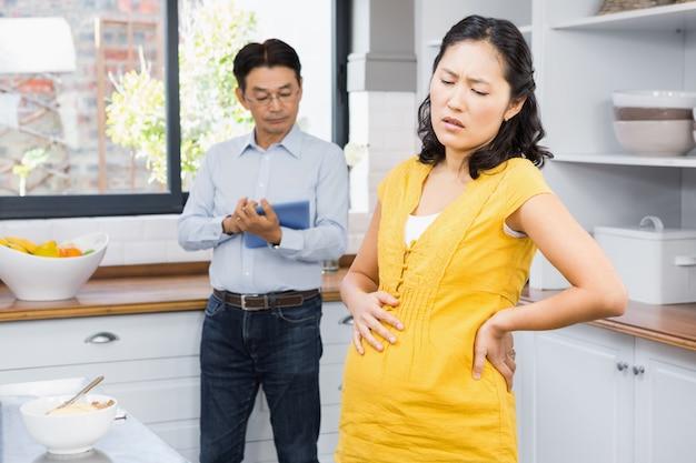 Femme enceinte souffrant de maux de dos dans les ktichen