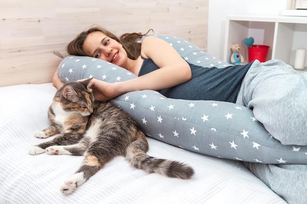 Femme enceinte souriante allongée à l'intérieur sur un lit sur un long oreiller et caressant son chat domestique