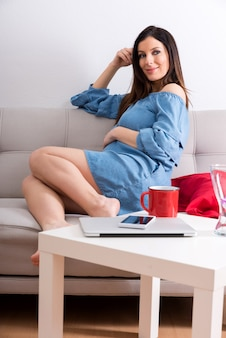 Une femme enceinte souriante assise sur un canapé et recouverte d'une couverture