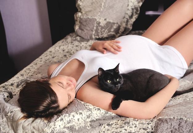 Femme enceinte souriante avec chat à la maison.