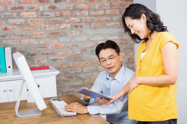 Femme enceinte souriante montrant une tablette à son mari à la maison