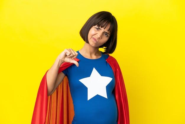 Femme enceinte de super héros isolée sur fond jaune montrant le pouce vers le bas avec une expression négative