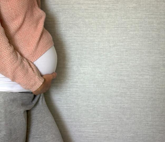 Une femme enceinte en t-shirt blanc et un pull rose tient son ventre sur fond gris