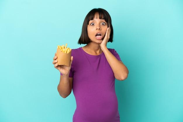 Femme enceinte tenant des chips frites sur fond isolé avec une expression faciale surprise et choquée
